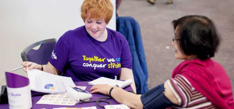 A member of Stroke Association staff offering free blood pressure checks at one of our events