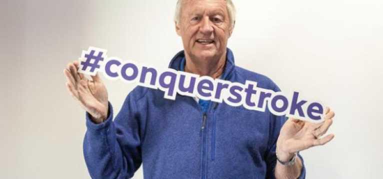 Chris Tarrant holding a #conquerstroke sign