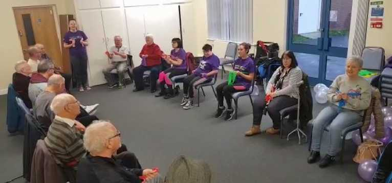 A room with people divided on both sides of the room, sitting on chairs