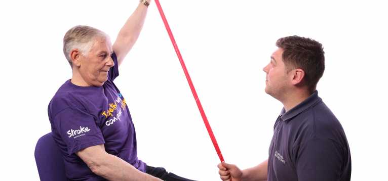 Stroke survivor using a resistance band with a physiotherapist