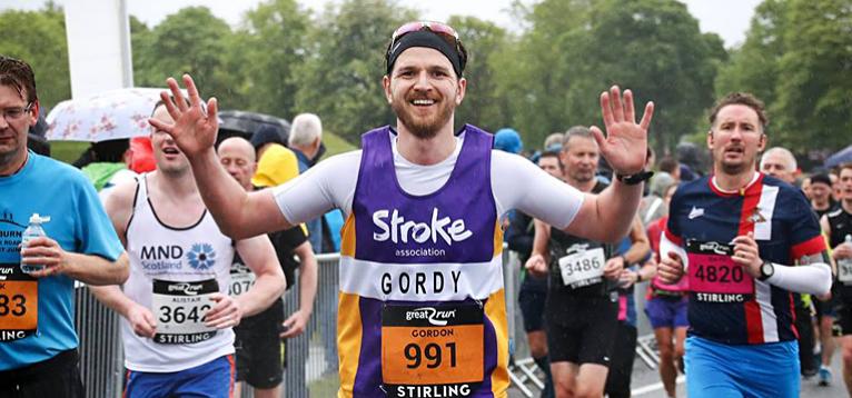 A runner running in a race wearing a purple stroke association vest