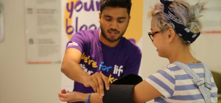 Young woman having her blood pressure tested