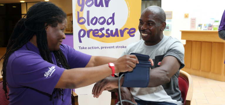 A stroke association employee delivering a blood pressure check