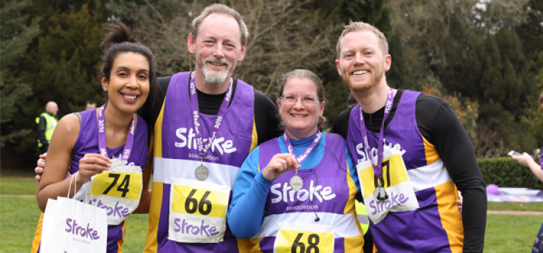 Volunteers who ran in last year's resolution run holding their medal and wearing their Stroke Association vest