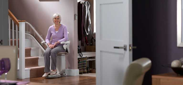 A woman using a Stannah stairlift