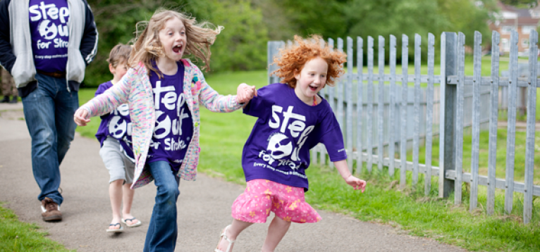 Two girls running and laughing at a Step out for Stroke event