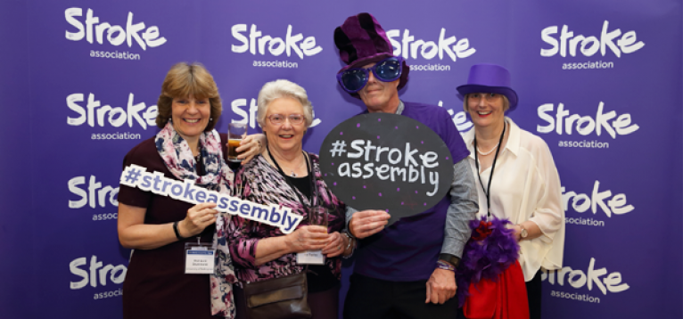 Visitors of the UKSA wearing purple hats, sunglasses and holding our stroke assembly hashtag sign