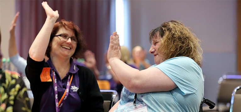 Two delegates giving each other a high five