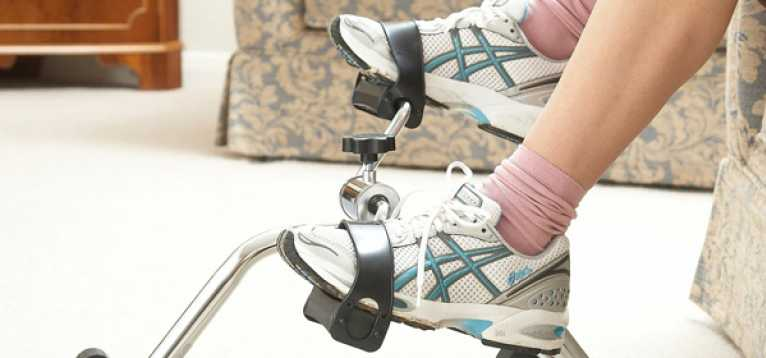 A woman using a foot pedal exercise machine