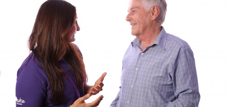 Stroke survivor standing and talking to a life after stroke coordinator