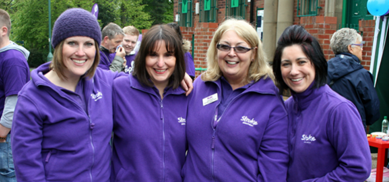 Four volunteers from tameside in purple stroke association jackets