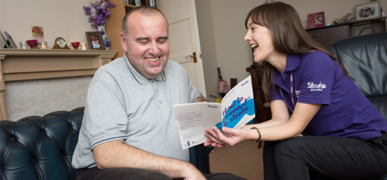 Stroke coordinator with a stroke survivor in their home, talking through an information leaflet.