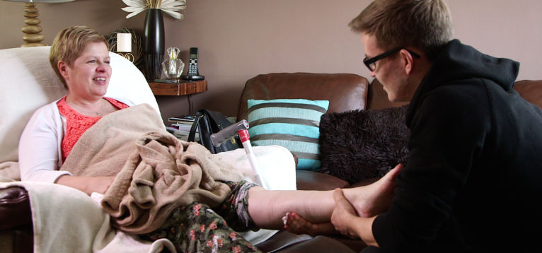 Carer Will massages his mother's leg