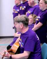 A group singing with a guitarist in purple stroke association t-shirts