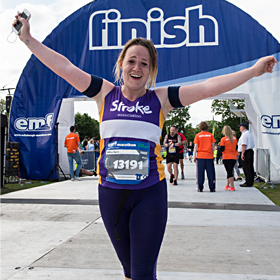 A marathon runner celebrating finishing with their hands in the air