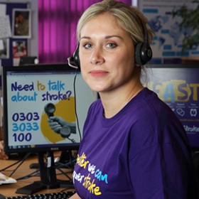 A member of our helpline team, smiling at their desk