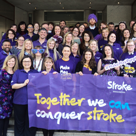 Staff at Stroke Association house on the front steps wearing purple t-shirts