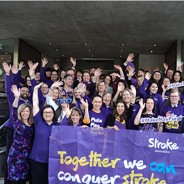 Stroke Association employees outside head office all dressed in purple
