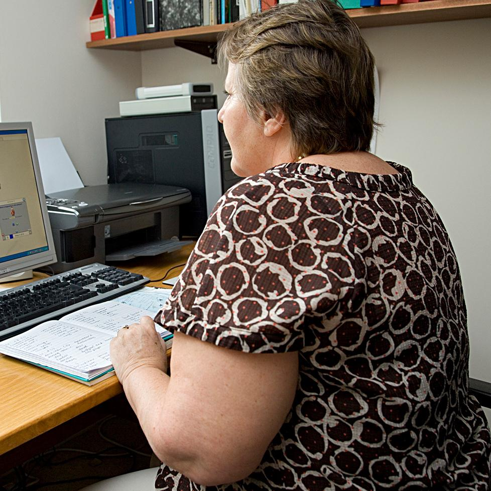 A woman sitting at a desk, working on her computer.