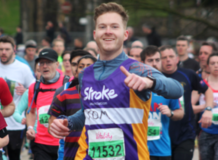 Runner in a stroke association vest smiling with his thumbs up