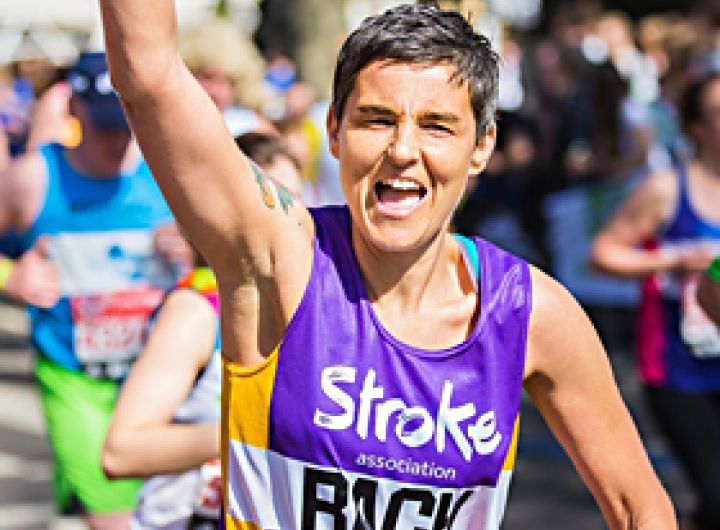 A runner in a stroke association vest running with his arm up smiling