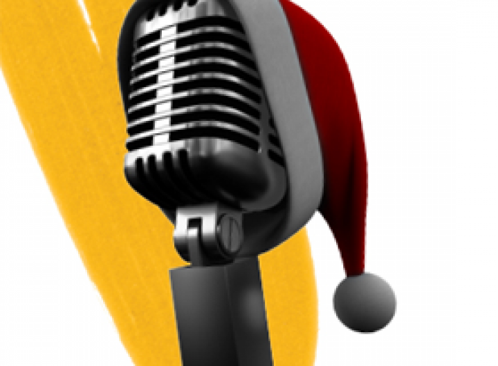 A stand up microphone with a santa hat on top