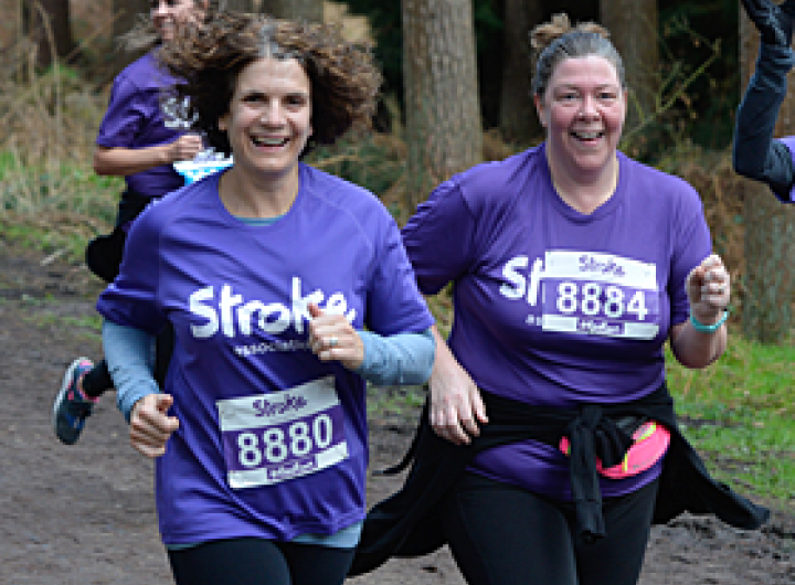 Two women running in purple t shirts and smiling
