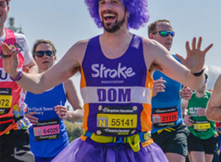 A runner dressed in a purple wig and tutu, running for us in last year's Brighton Marathon