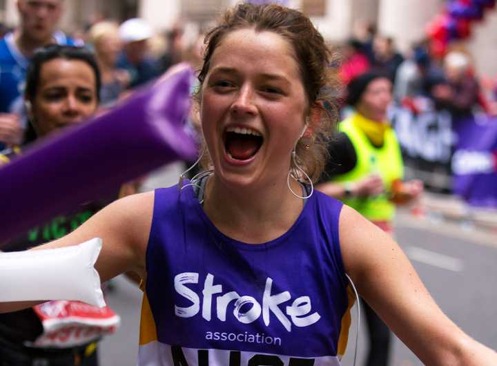 London marathon event runner with her arms spread out