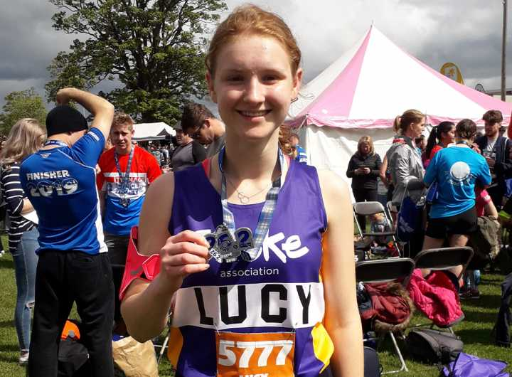 Lucy Cogley, an event runner, holding a medal around her neck.