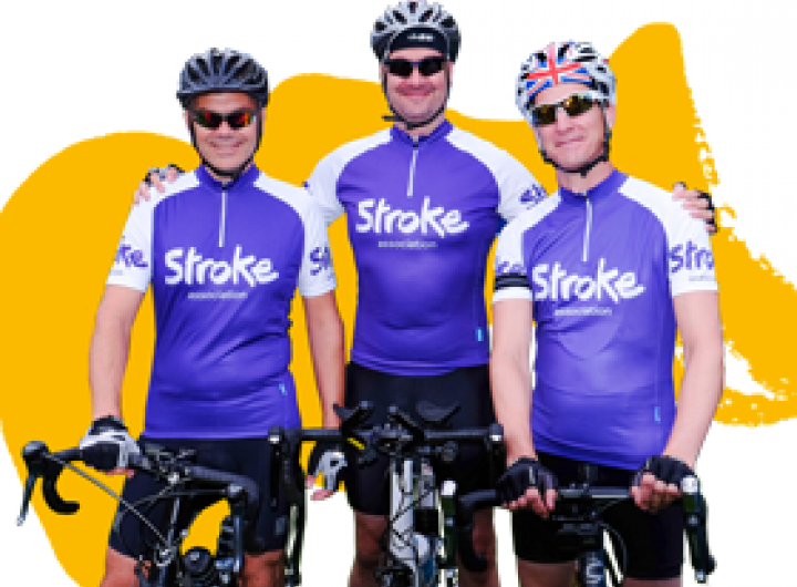 Cyclists dressed in purple getting ready to ride