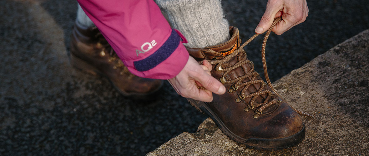 A close-up of a person tying the shoe laces of a brown boot that they are wearing. Their shoe is propped on top of a stone slab.