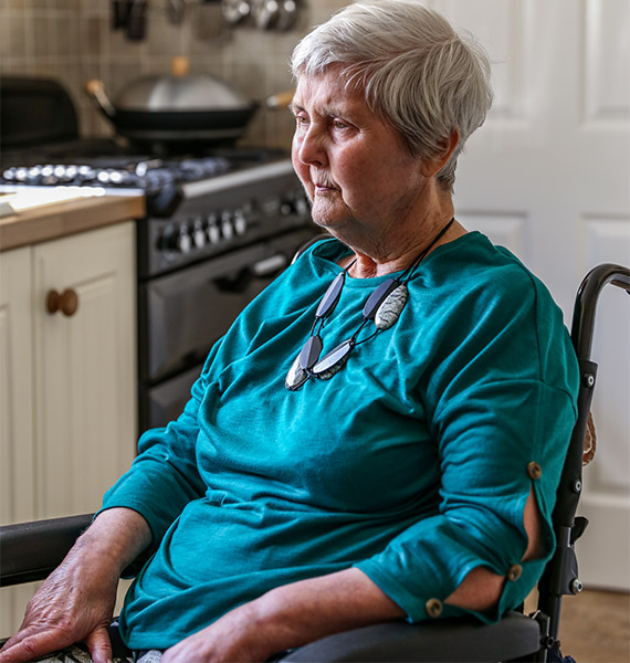 Woman sitting on a wheelchair in a kitchen