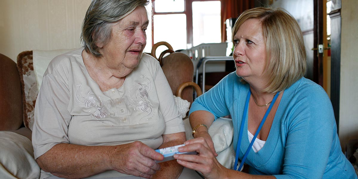 Woman receiving medication from another woman